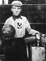 B/W Photograph of Len Grant in cap and shirt holding ball next to trophy