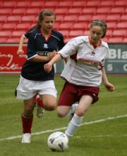 Two girls playing football, one is trying to tackle the other for the ball