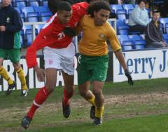Two footballers competing for possession of the football