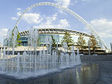 Photograph of public fountains in foreground and Wembley Stadium in the distance
