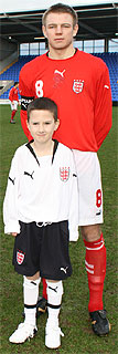 Photo of an England Schoolboy player with Mascot standing in front of him